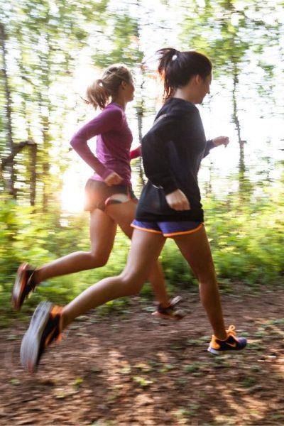 duas mulheres correndo na trilha